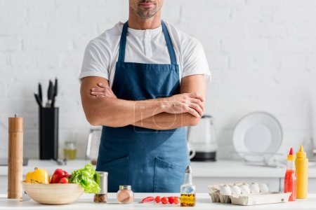 Photo for Man in apron standing on kitchen with crossed arms - Royalty Free Image