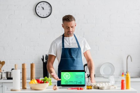 adult man with open laptop and online shopping illustration on screen standing at kitchen