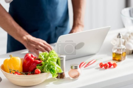 partial view of man working on laptop on white kitchen table