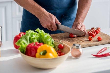 vue partielle de tomates-cerises coupe homme sur planche à découper sur la cuisine