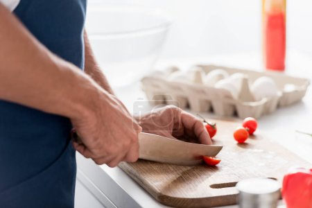 partial view of man cutting with knife cherry tomatoes on cutting board