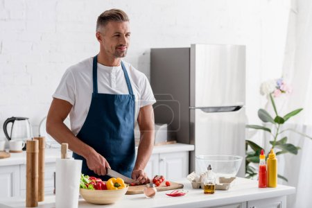 adult man cutting cherry tomatoes for salad on cutting board