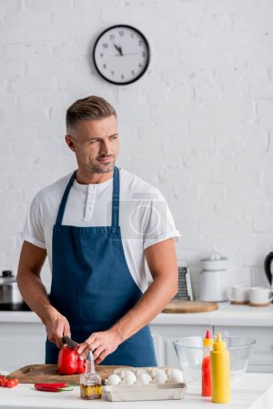 handsome adult man standing at kitchen and cutting red bell pepper
