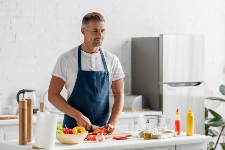 adult man standing at kitchen and making salad