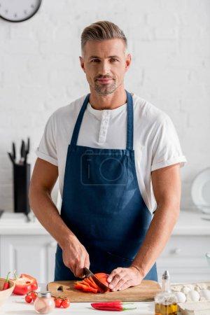 Photo pour Bel homme coupe le poivron sur la planche à la cuisine - image libre de droit