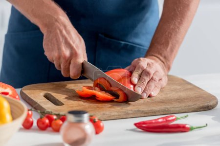 partial view of man cutting red bell pepper for salad
