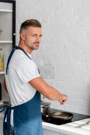 handsome man in apron salting steak on pan