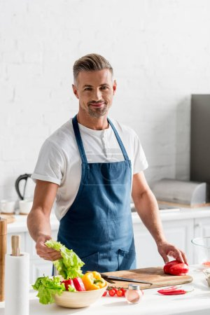 adult man standing at kitchen with salad ingredients on table