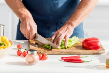 partial view of man cutting lettuce on chopping board for salad