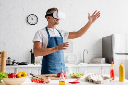 Photo for Adult cooker in virtual reality headset standing at kitchen - Royalty Free Image