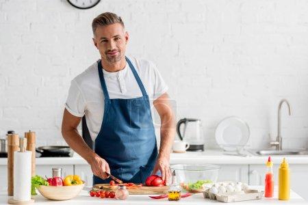 adult man slicing vegetables for salad at kitchen