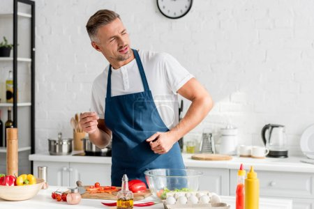adult man standing near table with ingredients at kitchen
