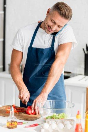 Photo pour Homme parlant sur smartphone tout en réduisant le poivron rouge en cuisine - image libre de droit