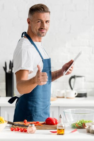 Photo for Man with digital tablet showing thumbs up at kitchen - Royalty Free Image