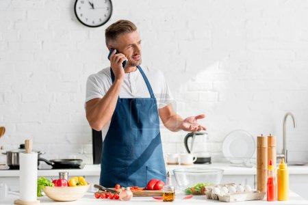 adult man speaking on smartphone at kitchen