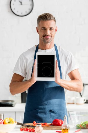 Photo for Adult man holding digital tablet with blank screen at kitchen - Royalty Free Image