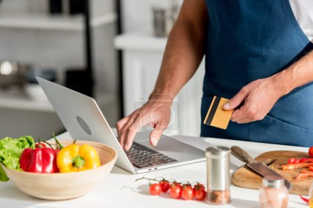 partial view of man in apron doing shopping online on laptop