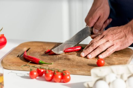 Photo for Close up view of male hands cutting chili peppers on chopping board - Royalty Free Image
