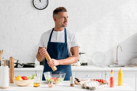 Photo pour Bel homme adulte dans la salade tablier salade à la cuisine - image libre de droit