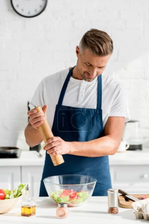 handsome adult man in apron salting salad at kitchen