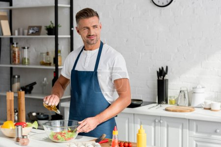 adult smiling man adding oil in salad at kitchen