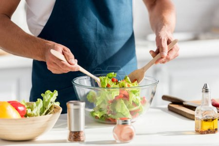 partial view of male cooker mixing salad