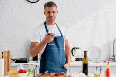 Photo pour Homme adulte avec verre de vin debout près de la table de cuisine - image libre de droit