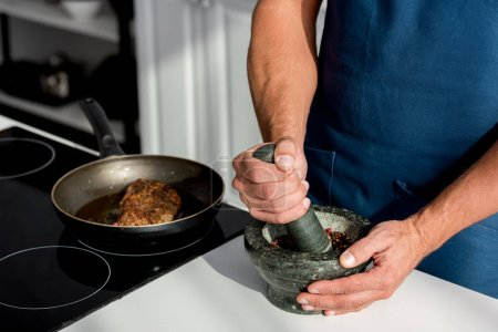 partial view of male hands crushing spices on kitchen table