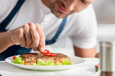 close up view of adult man adding peper to cooked steak
