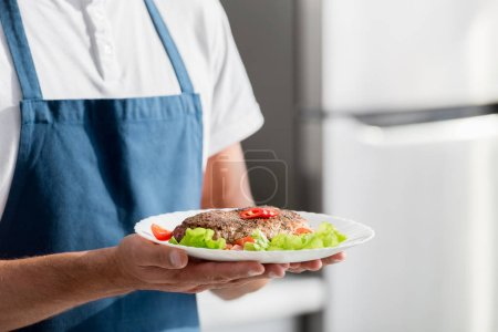 cropped view of man with cooked steak and vegetables on plate