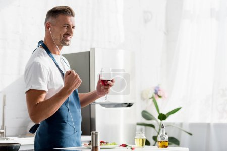smiling man with glass of wine listening to music at kitchen