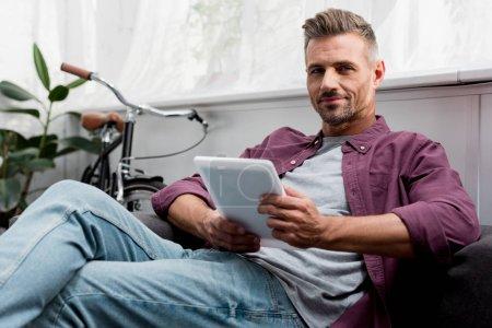 Photo pour Homme assis sur le canapé avec tablette numérique au bureau à la maison - image libre de droit