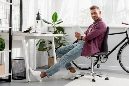 Photo for Relaxing man sitting on chair with digital tablet at home office - Royalty Free Image