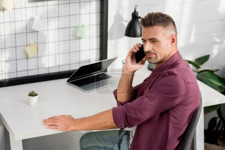 man sitting on chair and speaking on smartphone at home office