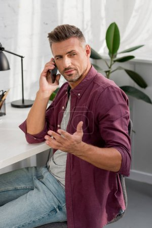 handsome man sitting on chair and speaking on smartphone at home office