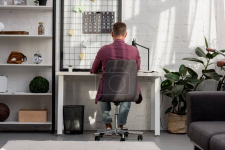 back view of man sitting on chair and working at home office