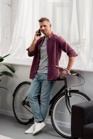 man talking on smartphone and leaning on bicycle at home office