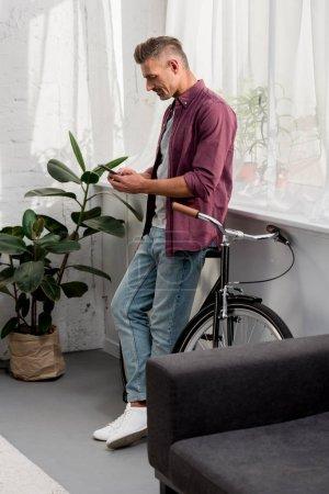 Photo pour Homme utilisant un smartphone tout en s'appuyant sur le vélo au bureau à la maison - image libre de droit