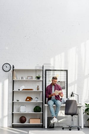 Photo for Smiling man sitting on table and reading book at home office - Royalty Free Image