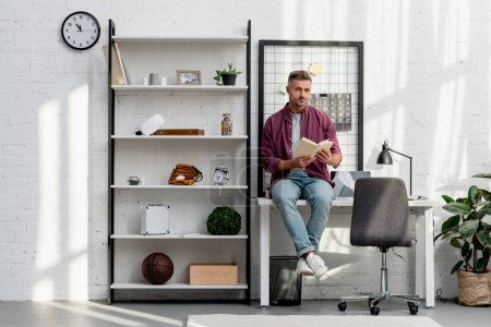 man sitting on table and reading book at home office