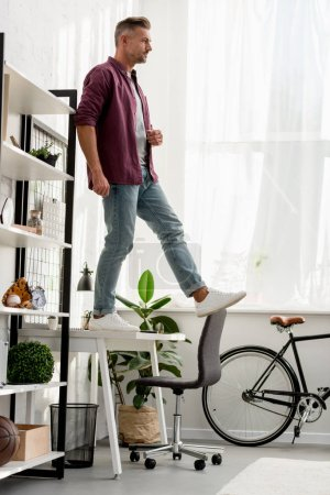 man stepping off table at home office