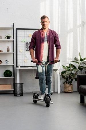 smiling man riding scooter at home office