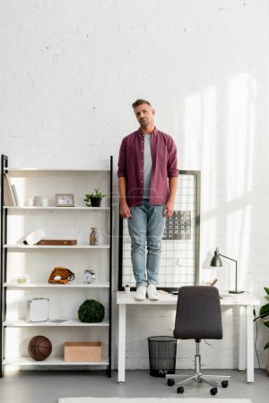 man with tired face standing on table at home office