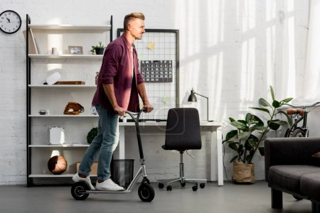 handsome man riding scooter at home office