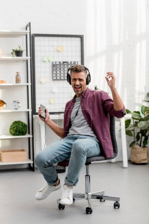 man listening music and singing loud while sitting on chair at home office