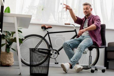 relaxed man throwing trash in basket