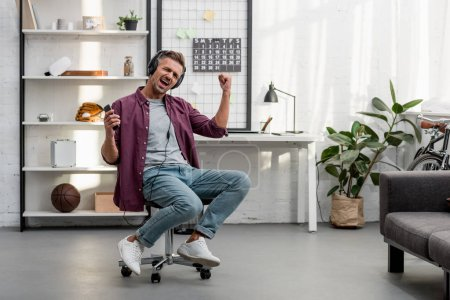 happy man listening music and singing while sitting on chair at home office