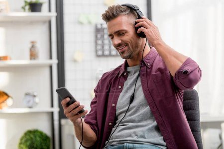 happy man listening music while sitting on chair at home office