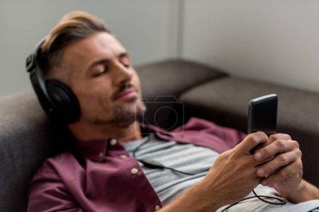 Photo pour Homme heureux avec smartphone et les yeux fermés, écoutant la musique tout en jetant sur le canapé - image libre de droit
