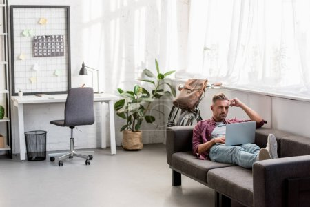 thoughtful man laying on sofa and working on laptop at home office